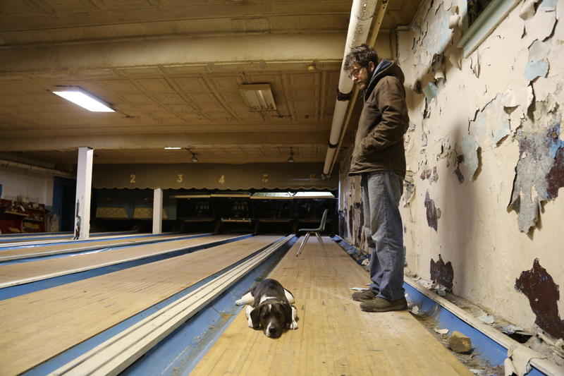 Workingmen's Beneficial Union owner Bill Brittain stands in the site's old bowling alley, soon to reopen as an event space. Brittain's dog Atlas has guarded the site throughout renovation.