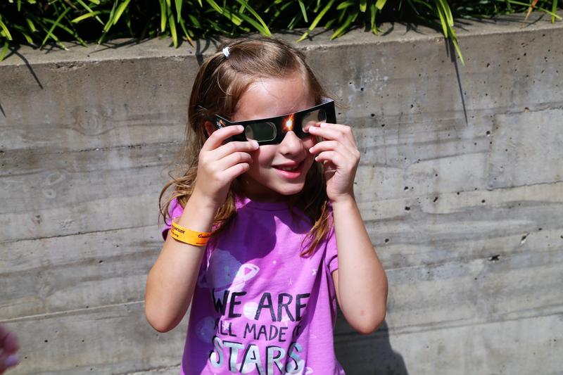 Sophia Defries, 6, adjusts her eclipse glasses outside the Children's Museum of Pittsburgh just before the solar eclipse on Monday, Aug. 21, 2017. Pittsburgh saw about 80 percent of the sun disappear.