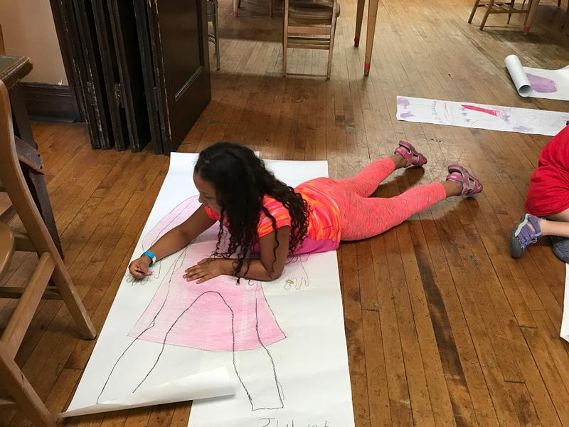 "Nia, 8, colors her Juliet ""costume"" - designing costumes for characters is one of the week's activities"