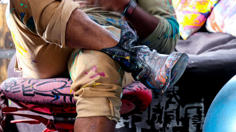The artist sports his signature paint-splatted garments while resting at his Point Breeze studio.