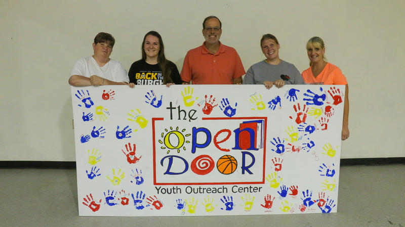 (Left to Right) Melody Shank, Marla Barrett, Dave Carver, Kristen Knouff and Pauline Bodnar Welsh hold up a painted sign at The Open Door in Crafton Heights