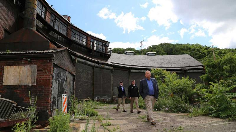 In this 2016 photo RIDC President Don Smith (right) walks in front of Almono's Roundhouse building. RIDC owns a former mill building on the site, where renovations are expected to begin soon. Potential reuse of the Roundhouse building is unclear.