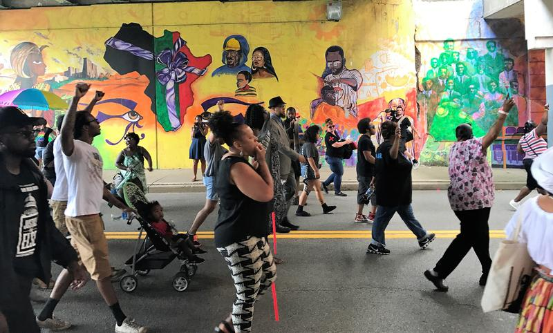 "Marchers walk down North Homewood Avenue, past the ""Peace Over Pittsburgh"" mural, by artists Ashley Hodder, Kristin DeGiovanni, Nicholas Hohman and Magil Sahara."