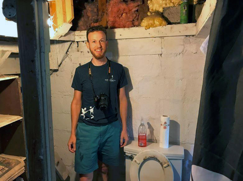 "Ted Zellers, of Lawrenceville, stands next to a ""Pittsburgh toilet,"" in the basement of a Crafton Heights home. He's photographing the local architectural oddities and hopes to use them in a coffee table book."