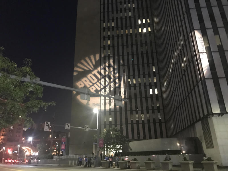 "Teachers, parents and activists gathered outside of the Federal Building Wednesday night under projections that read ""protect public education."" The group protested what they called an ""anti-public education agenda"" from the Trump administration."