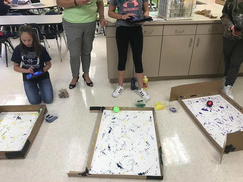 Students in the Innovate Ed class at Hopewell Junior High School use iPads to move robots through paint mimiking Jackson Pollock style paintings.