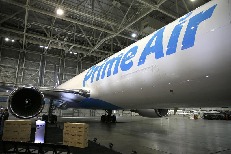"""Amazon.com boxes are shown stacked near a Boeing 767, an Amazon """"Prime Air"""" cargo plane on display Thursday, Aug. 4, 2016, in a Boeing hangar in Seattle."""