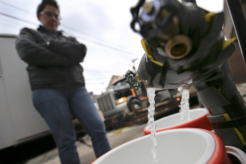 Ronette Cooley watches as water filles her gallon jugs at a city-owned water buffalo tank during a boil-water advisory for 100,000 Pittsburgh Water and Sewer Authority customers in February.