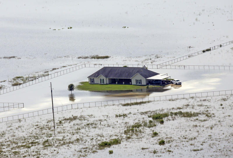A home is surrounded by floodwaters in the aftermath of Hurricane Harvey Friday, Sept. 1, 2017, near Winnie, Texas.