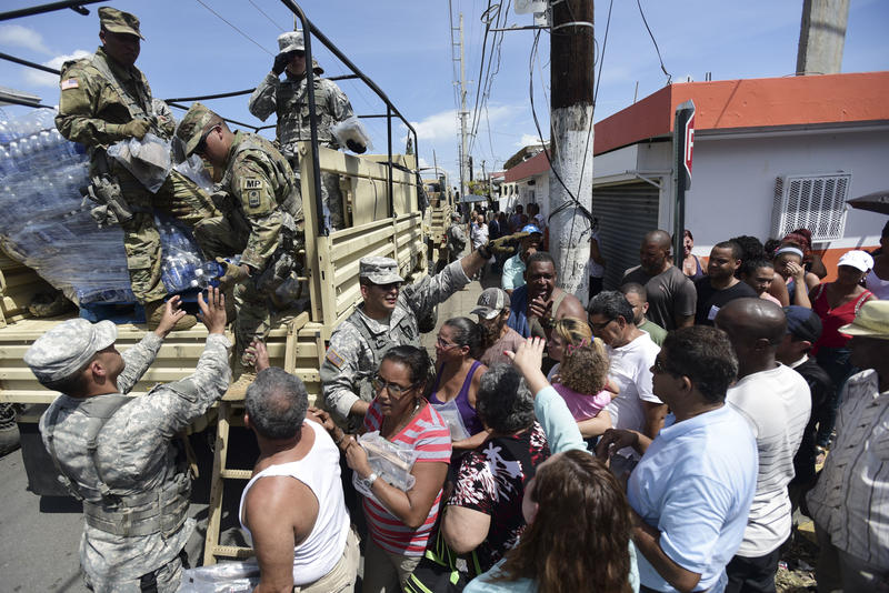 National Guardsmen arrive at Barrio Obrero in Santurce to distribute water and food among those affected by the passage of Hurricane Maria, in San Juan, Puerto Rico, Sunday, Sept. 24, 2017.