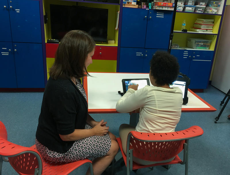 Satchel Heidelberg (right), a student at the Children's Institute and her therapist, Allison Dillon, remotely operate a Beam Smart Presence System and video-chat with American Eagle stylists.