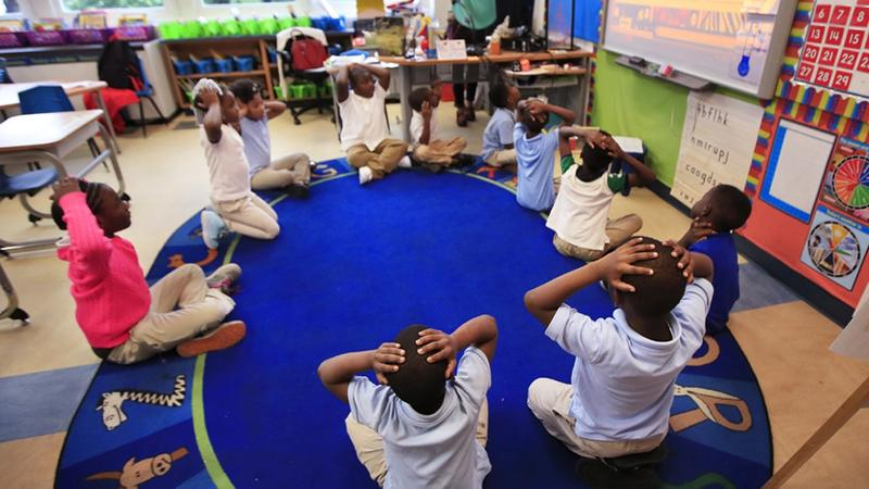 An elementary school teacher instructs students to put their hands over their heads.