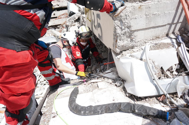 Roboticist Matt Travers, center, with two Mexican Red Cross workers, prepares to deploy the snakebot into a collapsed apartment building in Mexico City on Friday, Sept. 22, 2017. The snakebot is covered by a protective sheath.