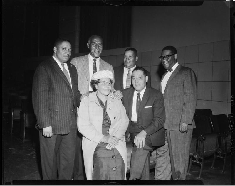 "Mary Ellen Hodge and Paul F. Jones seated, with Harry Fitzgerald, Robert E. ""Pappy"" Williams, Thomas J. ""Tommy"" Smith, and K. Leroy Irvis standing, in auditorium of A. Leo Weil School, June 1958. Jones was the first African American city councilor."