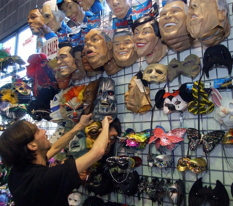 Cosmo Pace, an assistant manager at Costume World in Pittsburgh's Strip District, lines up a display of masks on the wall Monday, Oct. 4, 2004. After it was nearly cancelled, Pittsburgh's Bloomfield Halloween Parade will continue as scheduled this year.