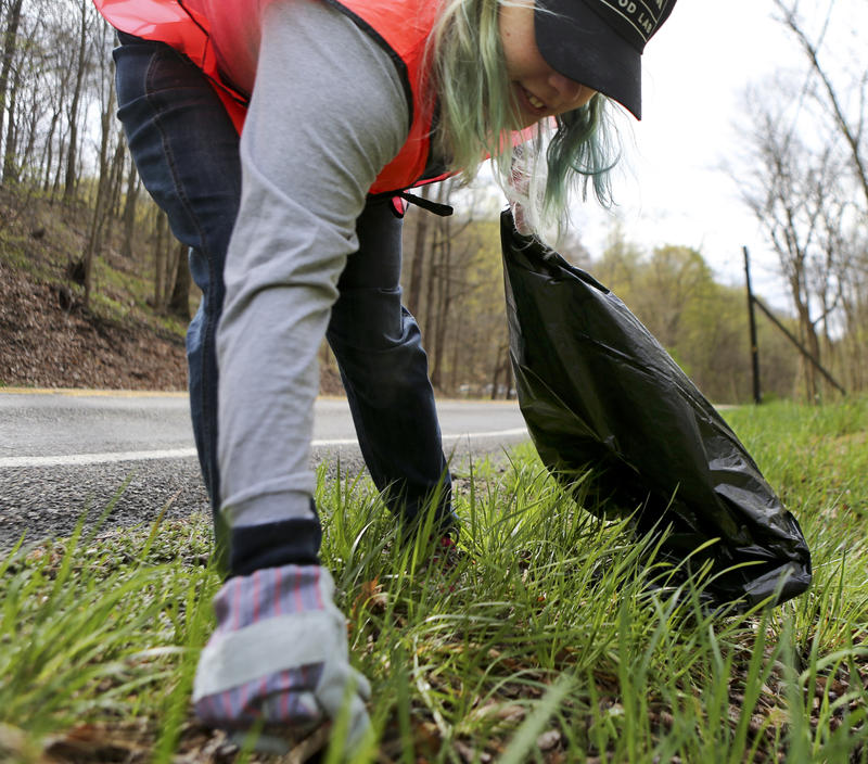 Lincoln Griffin, a volunteer with the Rachel Carson Trails Conservancy, picks up trash from the roadside along a portion of the trail named for ecologist author Rachel Carson.