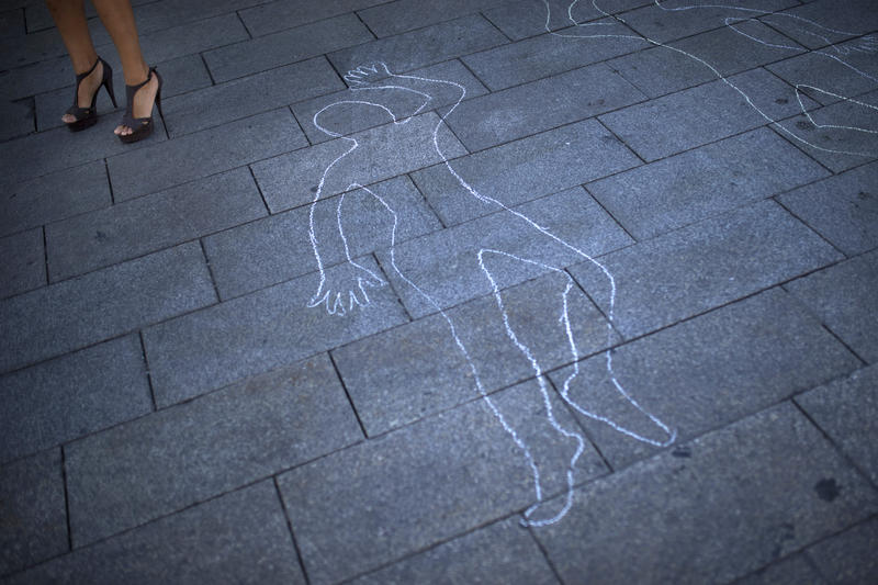 A woman stands by a drawing sketched on the ground, representing women killed by men, during a protest against violence against women in Madrid, July 25, 2017.