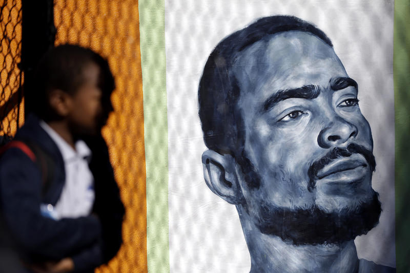 A young person views through a fence a painting of gun violence victim Shirkey Warthen before a ceremony commemorating Warthen with a new mural in Philadelphis in 2013. He was a member of Juvenile Law Center's youth advocacy program when he was killed.