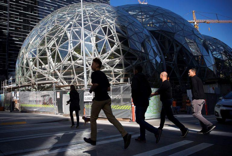 A group of joggers run by Amazon's first North American headquarters in Seattle, Wash.