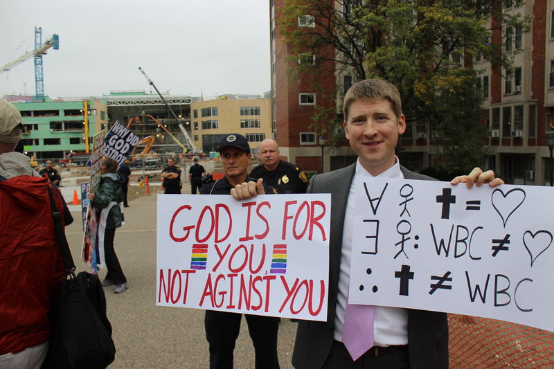 Nathan VanHoudnos, who recently started the group Christianity is Not Westboro Church, stands near three members of the Westboro Baptist Church as they protest LGBTQ people, Catholics, Jews, Islam and other religions on Thursday, Oct. 5, 2017.