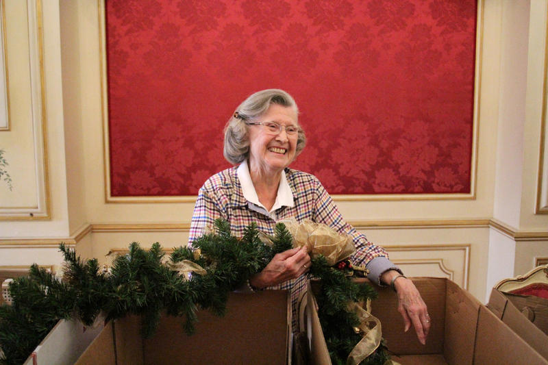 Joanne Weiss, member of the Austrian room committee, unpacks garlands on decorating day.