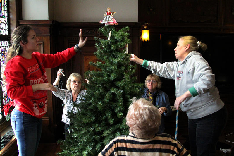 Members of the German room committee work to assemble and decorate the room's Christmas tree.
