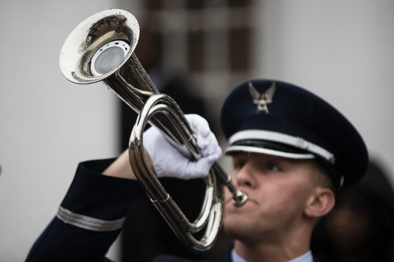 An Airman plays a recording of Taps on a ceremonial bugle outfitted with an electronic device after a funeral in Philadelphia, Friday, March 31, 2017.
