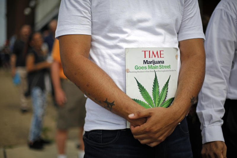 Michael Cole of Clairton, Pa., holds a Time magazine while waiting on line in downtown McKeesport, Pa., to attend a Medical Marijuana Job Fair, Thursday, July 27, 2017.