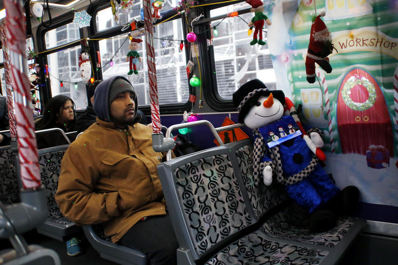 Passengers sit on the Christmas bus decorated by Port Authority driver Bill Sanfilippo, who has been decorating his rig since he was hired. He says it usually takes him 10 hours or more to put up all the lights, a life-sized Santa, Rudolph and more.