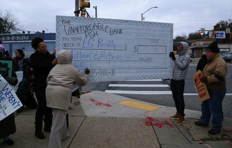 Alethea Sims, organizer and activist, writes on a blank check she says symbolizes the lack of money going toward affordable housing units in the city of Pittsburgh at a rally in East Liberty on Thursday, Nov. 16, 2017.
