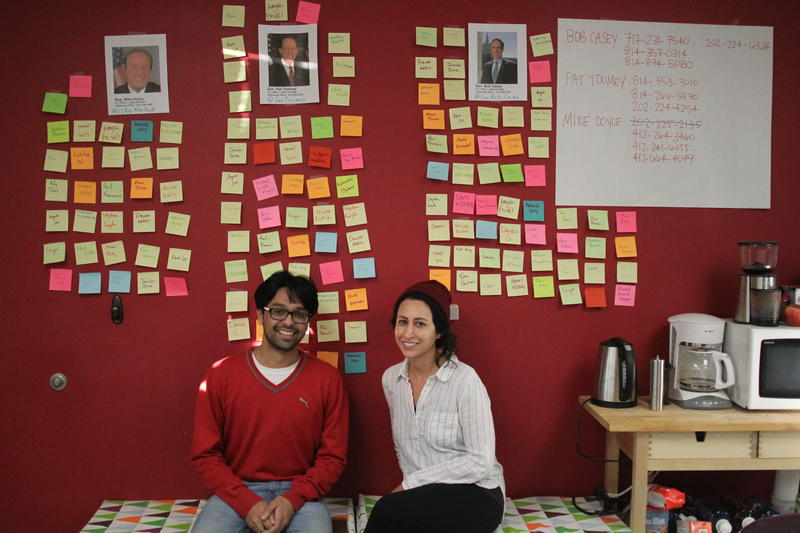 Surya Aggrawal, VP or external affairs for CMU's Graduate Student Assembly, and Brittani McKenna, the GSA Aadministrative coordinator, sit in front of a wall full of names of students who have called their representatives.