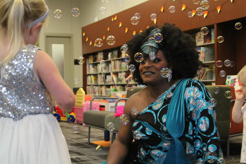 Tesla Patsilevas, 4 of Allison Park, left, talks to Akasha Lestat Van-Cartier, right, after a drag story hour at the Carnegie Library's North Side branch.