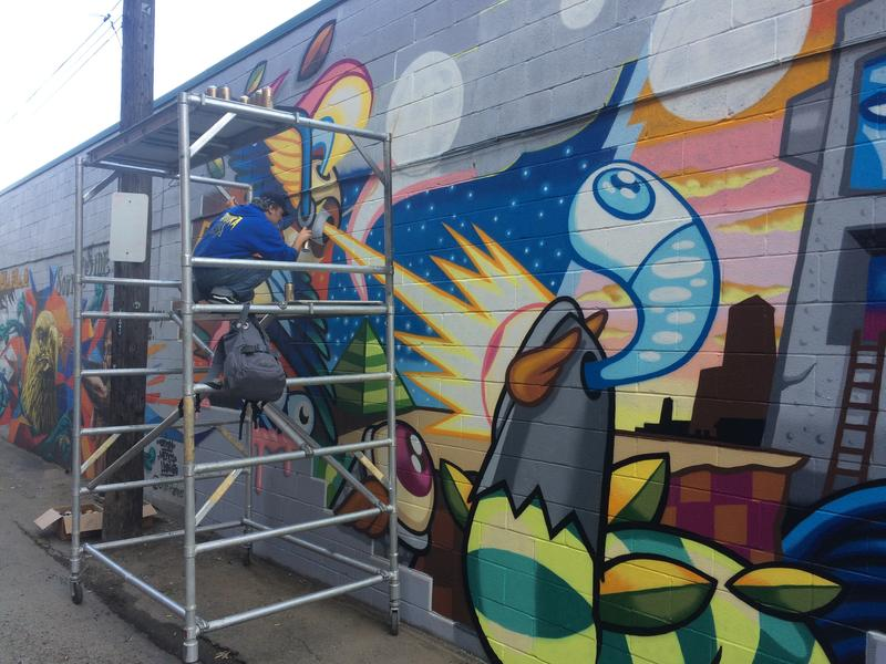 Plum artist Matt Spahr puts on some finishing details to his mural on Fox Way in late October.