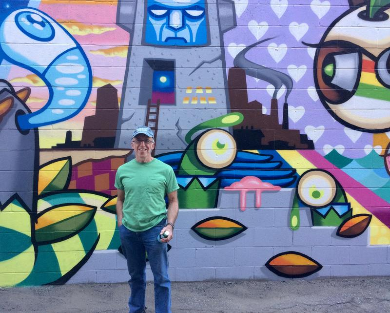 South Side volunteer Steve Root stands in front of a mural by Plum artist Matt Spahr.