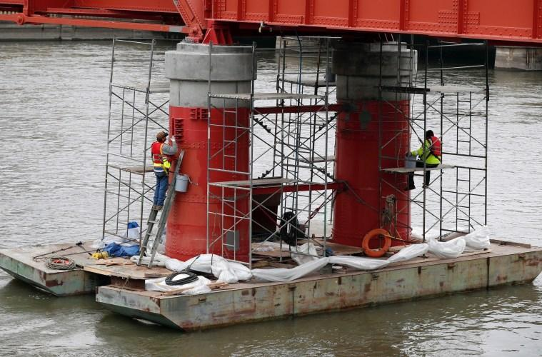 In this photo from March 28, 2017, work is done on the red bridge pedestrian bridge over the Des Moines river in Iowa.