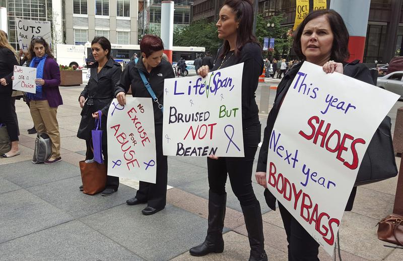 In this Oct. 1, 2015 file photo, advocates for victims of domestic abuse protest outside of state offices in downtown Chicago.