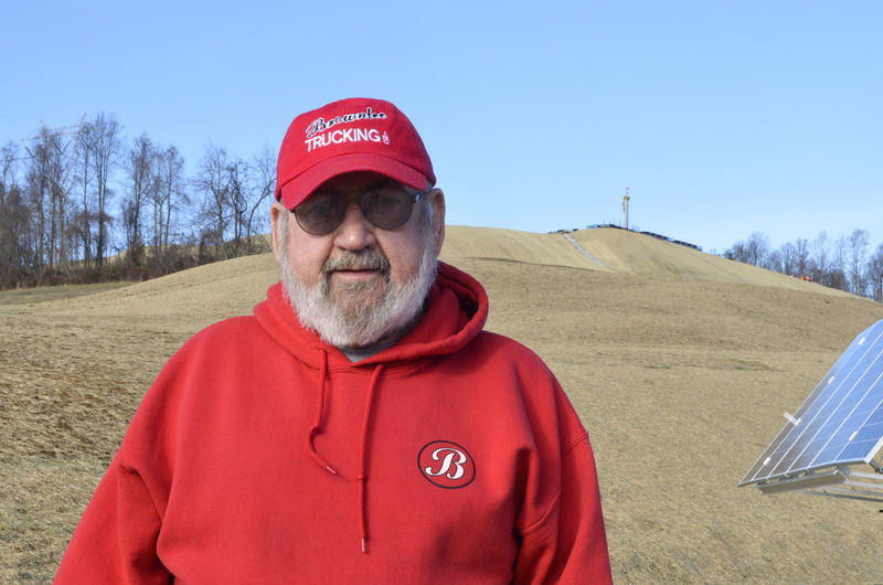 Washington County resident Frank Brownlee stands behind his house, where a rig on the hill behind him is drilling natural gas wells.