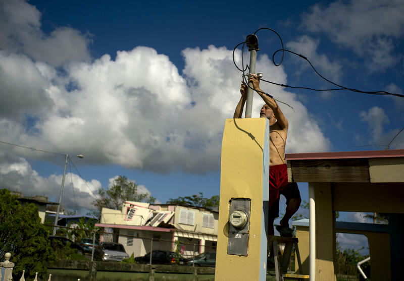 In this Friday, Oct. 13, 2017 photo, a resident tries to connect electrical lines downed by Hurricane Maria in preparation for when electricity is restored in Toa Baja, Puerto Rico.