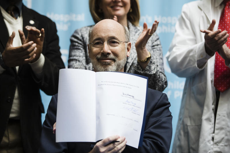Gov. Tom Wolf shows his signature after he signed legislation reauthorizing Pennsylvania's Children's Health Insurance Program at Children's Hospital of Philadelphia on Friday, Dec. 15, 2017.