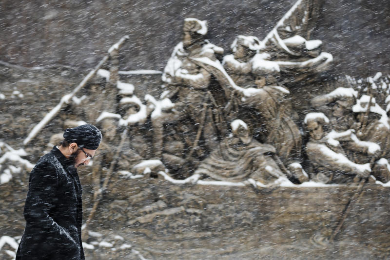 A man walks during a snowstorm past a sculpture of General George Washington crossing the Delaware River mounted on the Museum of the American Revolution in Philadelphia, Friday, Dec. 15, 2017.