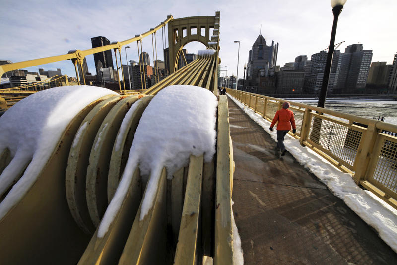 A woman walks across the Roberto Clemente Bridge over the Allegheny River in downtown Pittsburgh.