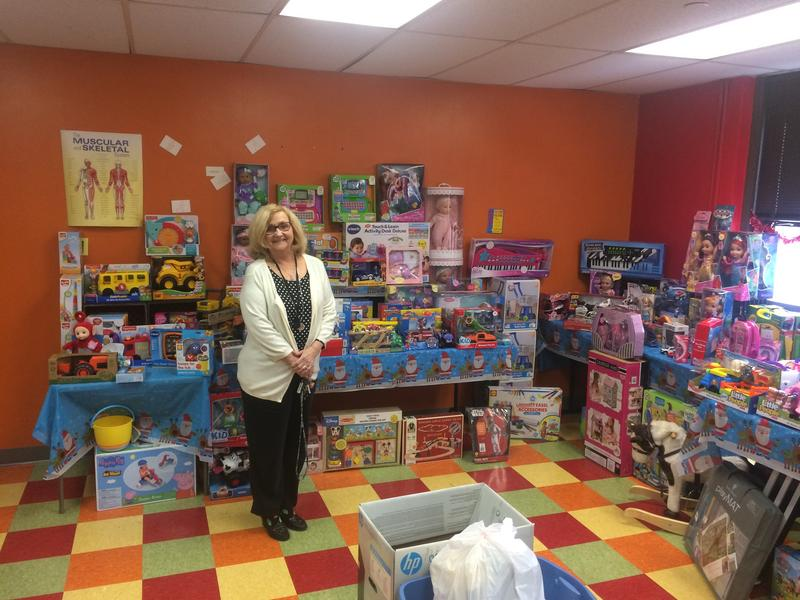 Sue Otto, director of the Center for Hope in Ambridge, stands amid the Christmas toys donated for local, low-income youth.