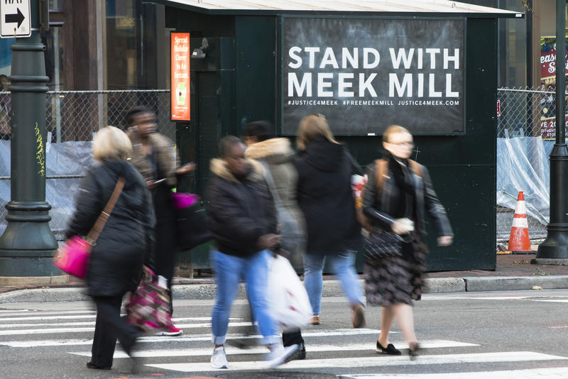 People walk past a placard posted on a newsstand with a message of support for imprisoned rapper Meek Mill, in Philadelphia, Friday, Dec. 1, 2017.