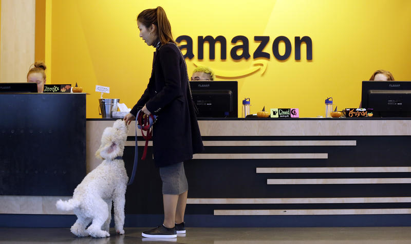 An Amazon employee and her dog walk into a building at the company's Seattle headquarters. Local officials wanted to keep secret their proposal to attract the online retailer.