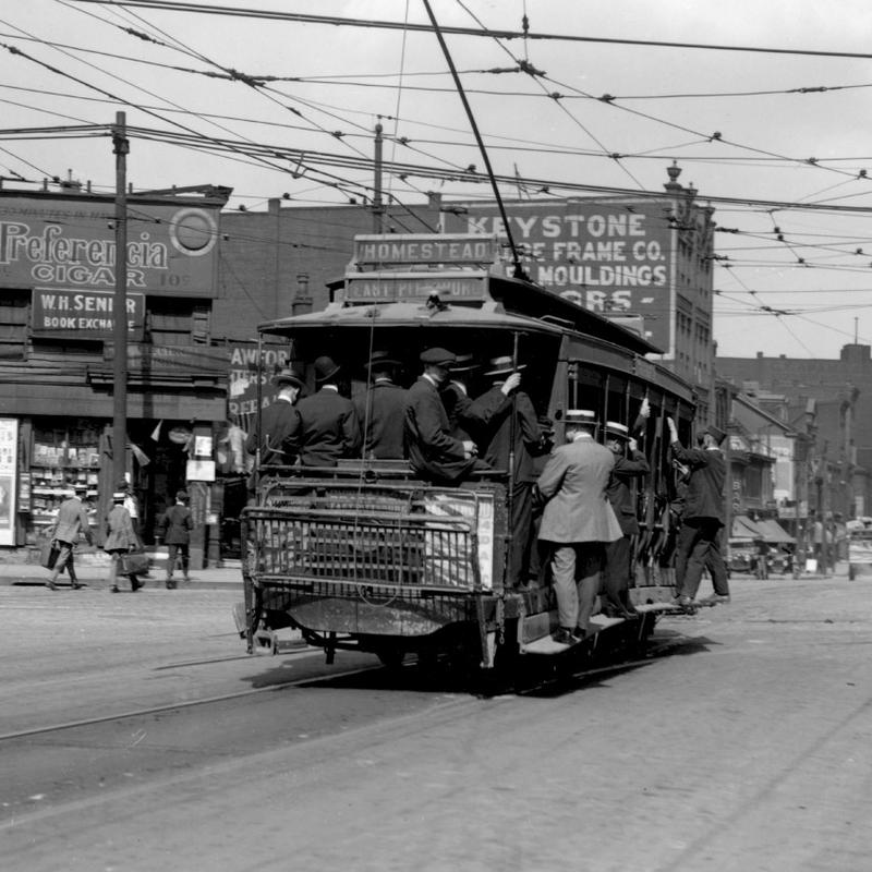 Men ride in an open car streetcar down a busy street in Pittsburgh. This route traveled from Homestead to East Pittsburgh.