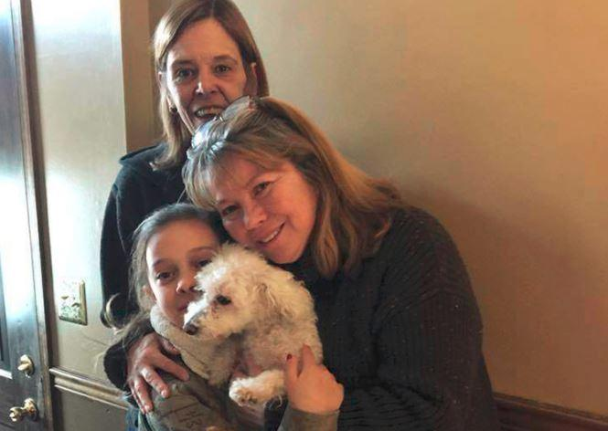 In this photo provided by Jessica Hartman, Monica Newhard, right, and her granddaughter, Helen Welch, hold their pet bichon frise, Zoey, as the dog's rescuer, Christina Hartman, stands behind them.