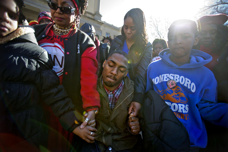 Leon Ford, center, joins hands with children during a rally in memory of Kendrick Johnson, a south Georgia teenager found dead in 2013, after investigators ruled he died in a freak accident.