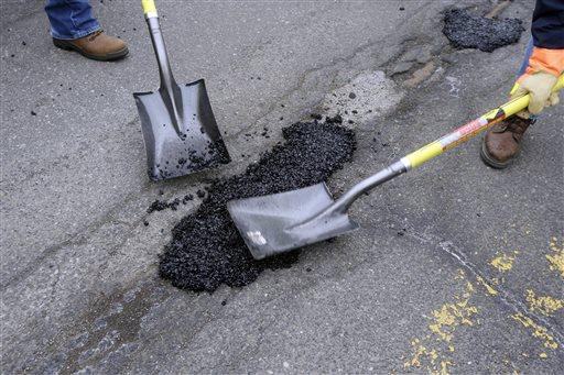 In this April 23, 2015 file photo, a pothole is patched in Detroit.