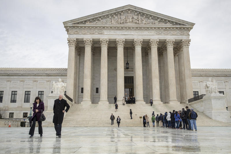 People stand on the plaza of the U.S. Supreme Court in Washington to attend arguments, Tuesday, Jan. 9, 2018.
