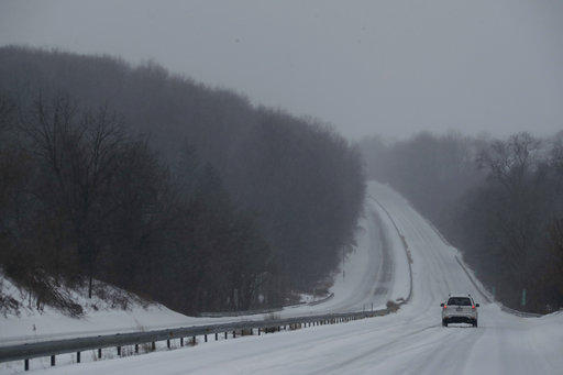 A car drives down US 30 through a winter snow storm.  Due to the bitter cold and snow, the Pennsylvania Turnpike has lowered speed limits.